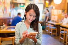 Woman using cellphone inside japanese restaurant Royalty Free Stock Photography