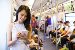 Woman using cellphone inside train compartment Royalty Free Stock Images