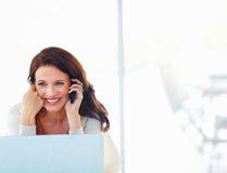 Woman using cellphone with laptop in front Stock Photo