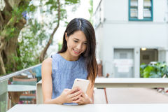 Woman using cellphone in outdoor cafe. Asian young woman Royalty Free Stock Photos
