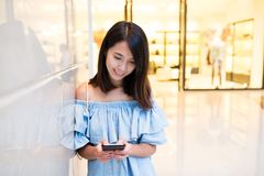 Woman using cellphone in shopping mall. Skyscraper building at outdoor Stock Photography