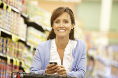 Woman using cellphone in supermarket Stock Photos