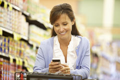 Woman using cellphone in supermarket Stock Photo
