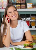 Woman Using Cellphone At Table In Supermarket Royalty Free Stock Photo