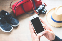Woman using cellphone with travel preparations on wood floor Royalty Free Stock Photos