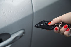 Woman using central locking remote to open car door. Stock Images