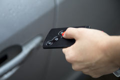 Woman using central locking remote to open car door. Stock Photos