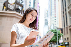 Woman using city map and cellphone Stock Photography