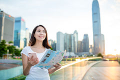 Woman using city map and cellphone to find the location Stock Images