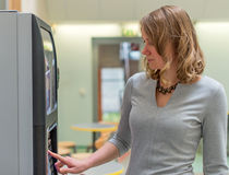 Woman using coffee vending machine. Royalty Free Stock Photos