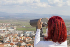 Woman using coin operated binoculars Royalty Free Stock Images