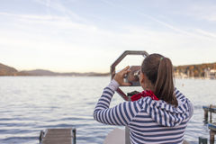 Woman using coin operated binoculars Royalty Free Stock Photos