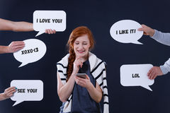 Woman using a communicator. Young smiling woman using a communicator on her smartphone royalty free stock images