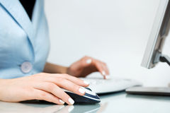 Woman using computer mouse and keyboard Stock Images