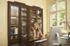 Woman Using Computer And Cellphone In Study Room. Smiling young woman using computer and cellphone in study room at home Stock Image