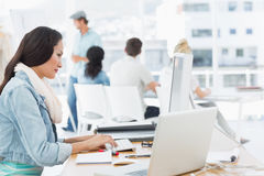 Woman using computer with colleagues behind in office Stock Photo