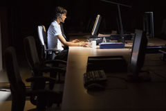 Woman Using Computer In Dark Office Stock Photo