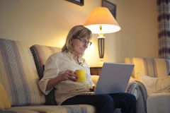 Woman using computer. Elder woman using computer at home drinking a coffee Royalty Free Stock Images