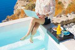 Woman using computer and having breakfast by the pool Stock Image