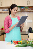 Woman using computer in her kitchen Stock Photography