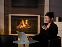 Woman using computer at home. Young woman sitting in front of fireplace at home on a cold winter day, working on laptop computer Royalty Free Stock Photography