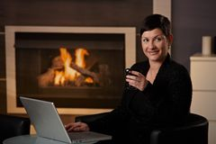 Woman using computer at home. Young woman sitting in front of fireplace at home on a cold winter day, working on laptop computer Stock Image
