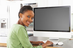 Woman Using Computer In Kitchen. Young Woman Using Computer In Modern Kitchen Royalty Free Stock Photography