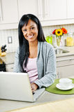 Woman using computer in kitchen. Smiling black woman using computer in modern kitchen interior Stock Photography
