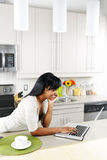 Woman using computer in kitchen Stock Images