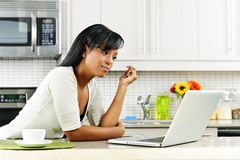 Woman using computer in kitchen. Thoughtful black woman using computer in modern kitchen interior Stock Photos