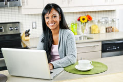 Woman using computer in kitchen. Smiling black woman using computer in modern kitchen interior Stock Photo
