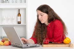 Woman using computer in the kitchen Stock Photos