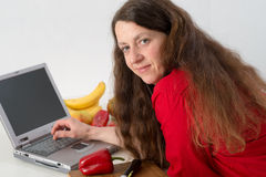 Woman using computer in the kitchen. Long-haired woman using computer in the kitchen Stock Photography