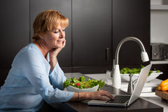 Woman using computer in kitchen Stock Photography