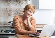 Woman using computer in kitchen Royalty Free Stock Photography