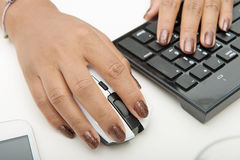 Woman using computer mouse and keyboard Stock Photo