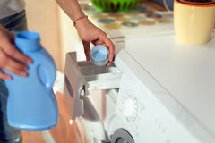 Woman using conditioner for washing machine Stock Images