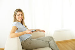 Woman using a control remote Stock Images