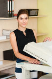 Woman using a copy machine Stock Photography