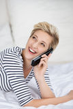 Woman Using Cordless Phone While Looking Up In Bed royalty free stock photo