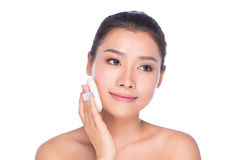 Woman using cosmetic sponge on face with smile Stock Photography