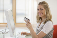 Woman using credit card and computer Stock Photography