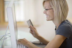 Woman using credit card and computer Royalty Free Stock Image