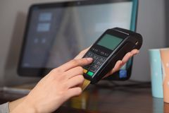 Woman using credit card machine for non cash payment in cafe, closeup. Space for text royalty free stock photo