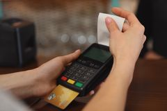 Woman using credit card machine for non cash payment in cafe, closeup. Space for text stock photography