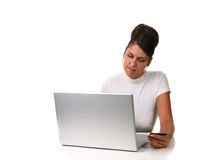 Woman using credit card online. Young woman sitting in front of a laptop with a credit card in her hand, isolated on a white background Stock Image