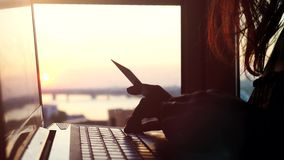 Woman using credit card online with her laptop on blurred city background during beautiful sunset and sun lense flare. Effects. 3840x2160. 4k stock video footage