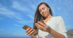 Woman using credit card on vacation shopping online with mobile phone at clear blue sea background. Woman using credit card on vacation shopping online with stock video footage