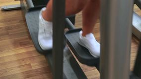 Woman using cross trainer. In gym stock video footage