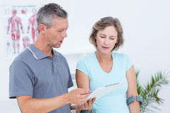 Woman using crutch and talking with her doctor Royalty Free Stock Images